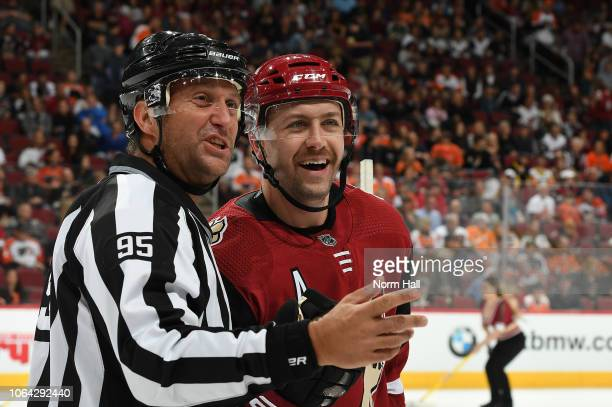 Derek Stepan of the Arizona Coyotes talks with linesman Jonny Murray during a stop in play against the Philadelphia Flyers at Gila River Arena on...