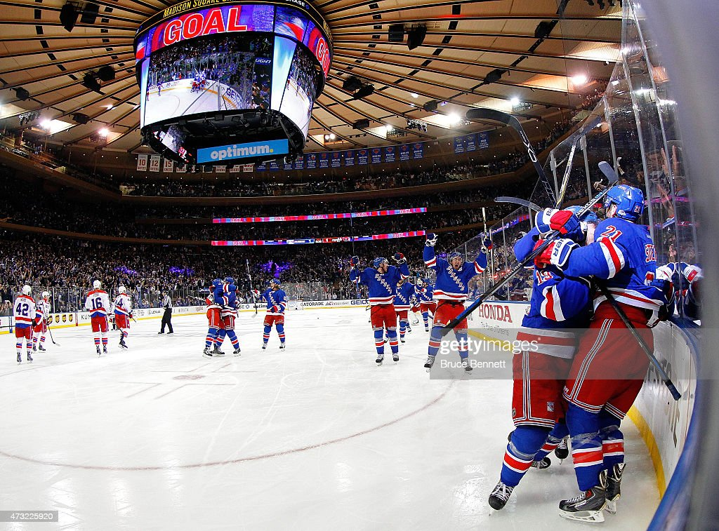 Derek Stepan #21 of the New York Rangers celebrates with his team after scoring the game winning goal in overtime against the Washington Capitals to win Game Seven of the Eastern Conference Semifinals by a score of 2-1 during the 2015 NHL Stanley Cup Playoffs at Madison Square Garden on May 13, 2015 in New York City.