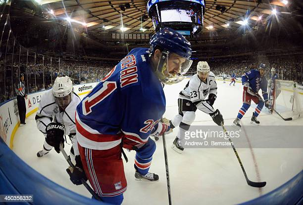 Derek Stepan of the New York Rangers is chased by Anze Kopitar and Dustin Brown of the Los Angeles Kings in the first period of Game Three of the...