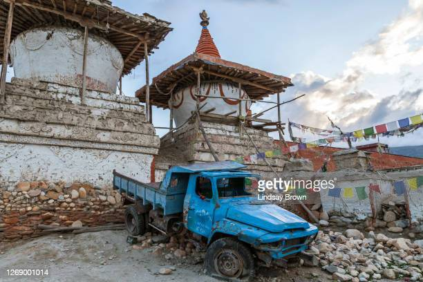 a derelict chinese truck from tibet lies abandoned behind a couple of ancient chortens in lo manthang. - lo manthang stock pictures, royalty-free photos & images