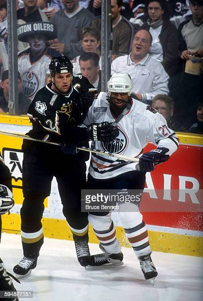 Derian Hatcher of the Dallas Stars battles with Georges Laraque of the Edmonton Oilers during Game 3 of the 2000 Conference QuarterFinals on April 16...
