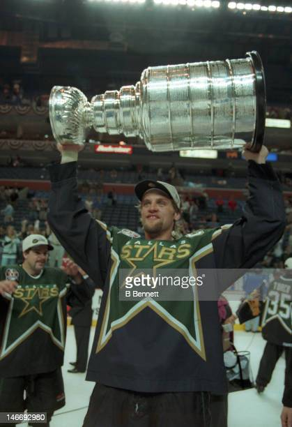 Derian Hatcher of the Dallas Stars celebrates with the Stanley Cup after the Stars defeated the Buffalo Sabres in Game 6 of the 1999 Stanley Cup...