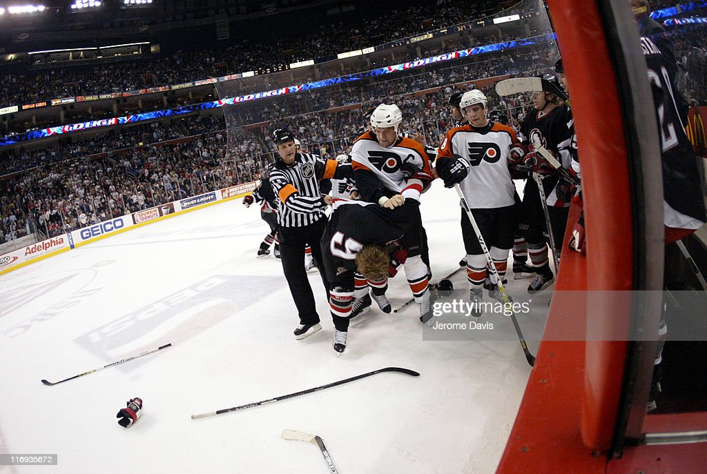 Derian Hatcher #2 of the Philadelphia Flyers tussles with Sabres' Derek Roy (on ice) during game two playoffs action versus the Buffalo Sabres at the HSBC Arena in Buffalo, NY, April 24, 2006. Buffalo defeated Philadelphia 8 -2 .
