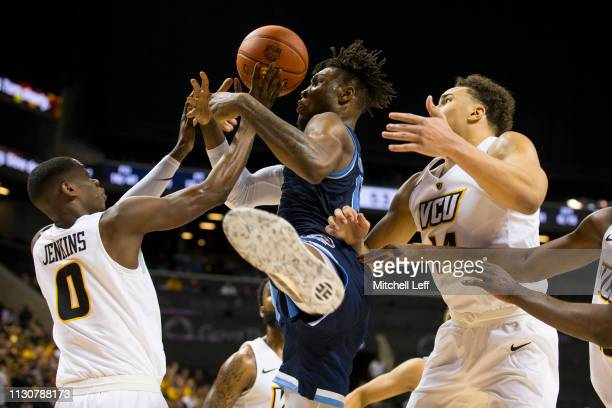 De'Riante Jenkins and Marcus SantosSilva of the Virginia Commonwealth Rams fight for the ball along with Cyril Langevine of the Rhode Island Rams...