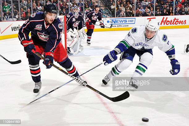 Derick Brassard of the Columbus Blue Jackets and Alexandre Burrows of the Vancouver Canucks chase after a loose puck during the third period on March...