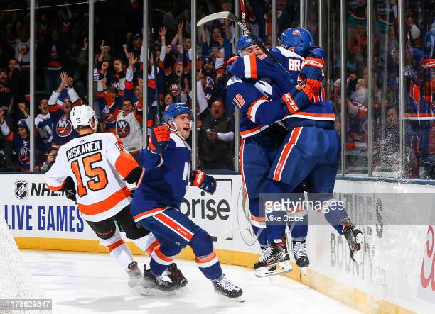 Derick Brassard of the New York Islanders is congratulated by his teammates Brock Nelson and Anthony Beauvillier after scoring a goal against the...