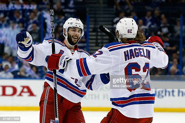 Derick Brassard of the New York Rangers celebrates with Carl Hagelin after scoring a goal on an empty net against the Tampa Bay Lightning during the...