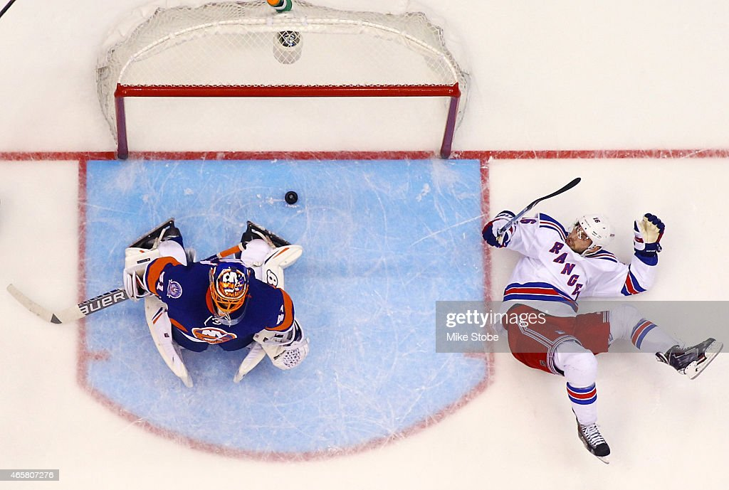 Derick Brassard #16 of the New York Rangers falls to the ice as Jaroslav Halak #41 of the New York Islanders allows a third period goal on a shot by Rick Nash #61 of the New York Rangers (not shown) at Nassau Veterans Memorial Coliseum on March 10, 2015 in Uniondale, New York.The New York Rangers defeated New York Islanders 2-1.