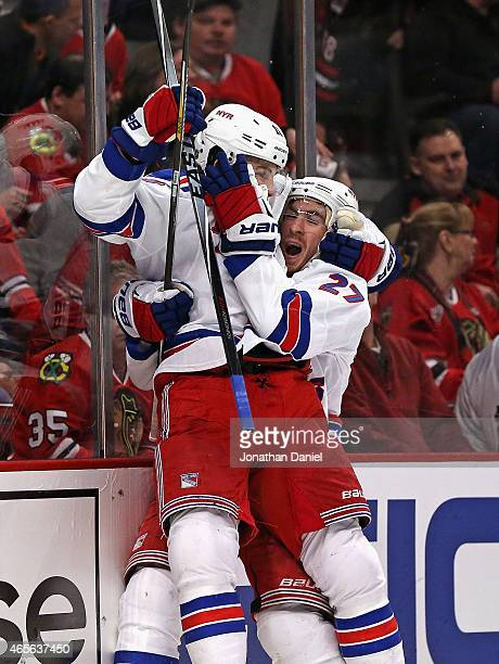 Derick Brassard of the New York Rangers jumps into the arms of teammate Ryan McDonagh as they celebrate Brassards' game winning goal in overtime...