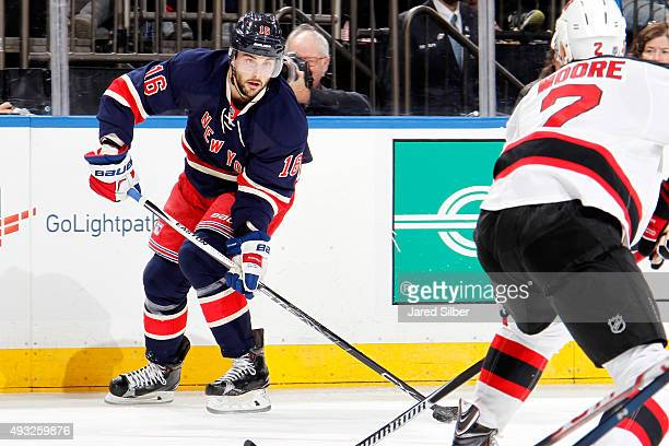 Derick Brassard of the New York Rangers skates with the puck against John Moore of the New Jersey Devils at Madison Square Garden on October 18 2015...