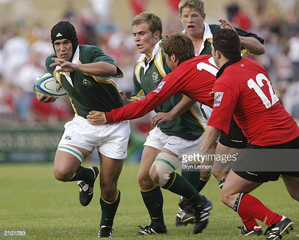 Derick Hougaard of South Africa avoids the Welsh defence of Nicky Robinson and Scott Williams during the IRB U21 World Cup game between South Africa...