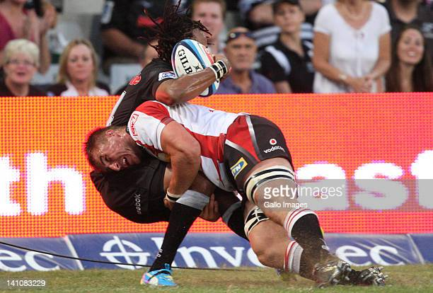 Derick Minnie of the Lions with a big hit on Odwa Ndunganeu of the Sharks during the Super Rugby match between The Sharks and MTN Lions at Mr Price...