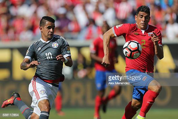 Derlis Gonzalez of Paraguay and Johnny Acosta of Costa Rica chase a loose ball during the 2016 Copa America Centenario Group A match between Costa...
