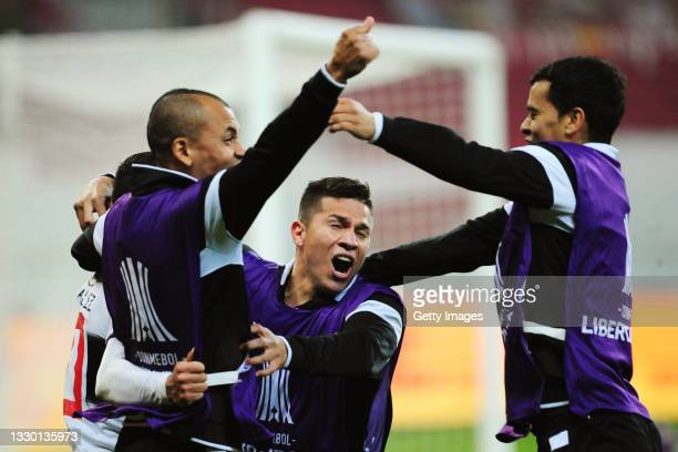 Derlis González of Olimpia celebrates with teammates after scoring the last penalty to qualify for the next round in the shootout after a round of...