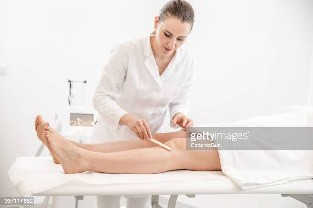 dermatologist applying gel to skin before diode laser hair removal - female body hair stock photos and pictures