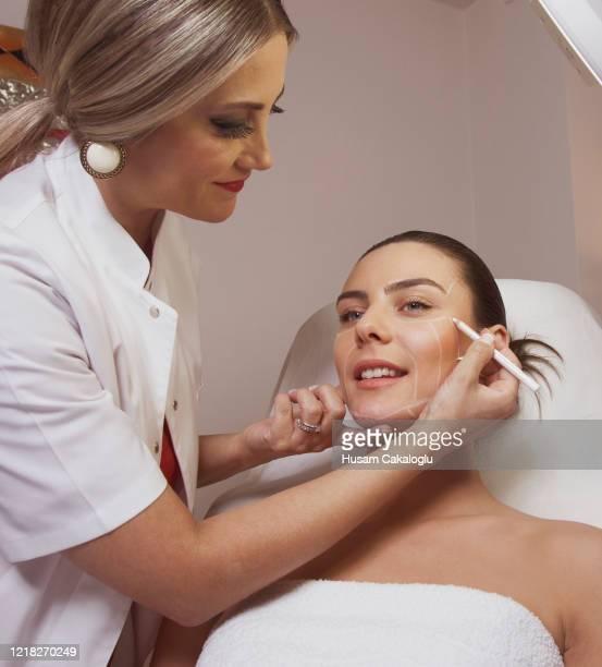 mujer dermatóloga cirujana dibujando líneas en la cara de la mujer para cirugía plástica - liposuccion fotografías e imágenes de stock