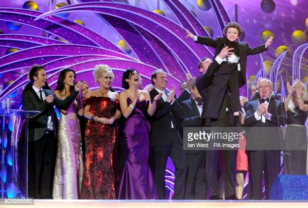 Dermot O'Leary hold up young actor Alex Bain as members of the Coronation Street cast collect the best Serial Drama award during the National...