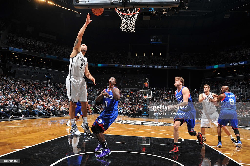Deron Williams #8 of the Brooklyn Nets drives to the basket against the Philadelphia 76ers at the Barclays Center on December 23, 2012 in Brooklyn, New York.