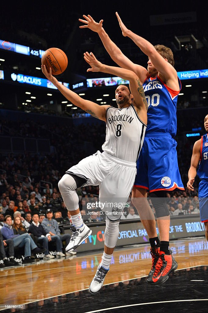 Deron Williams #8 of the Brooklyn Nets drives to the basket around Spencer Hawes #00 of the Philadelphia 76ers at the Barclays Center on December 23, 2012 in Brooklyn, New York.