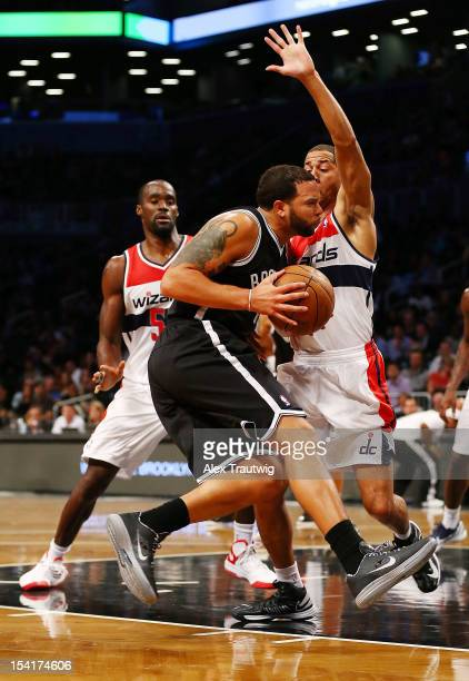 Deron Williams of the Brooklyn Nets drives to the basket as Jannero Pargo and Emeka Okafor of the Washington Wizards defends during a preseason game...