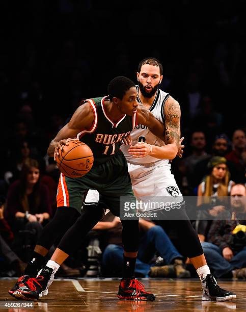 Deron Williams of the Brooklyn Nets guards Brandon Knight of the Milwaukee Bucks during the second overtime at the Barclays Center on November 19...