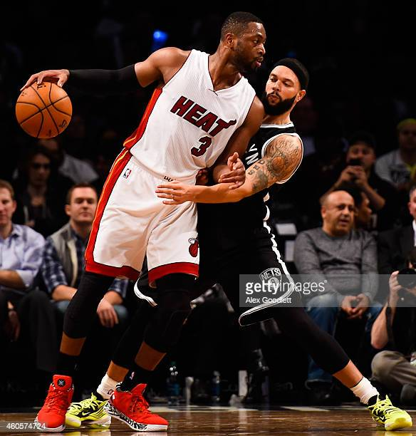 Deron Williams of the Brooklyn Nets guards Dwyane Wade of the Miami Heat in the second half at the Barclays Center on December 16 2014 in the...