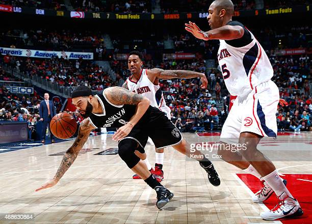 Deron Williams of the Brooklyn Nets loses the ball as he drives against Jeff Teague and Al Horford of the Atlanta Hawks at Philips Arena on April 4...