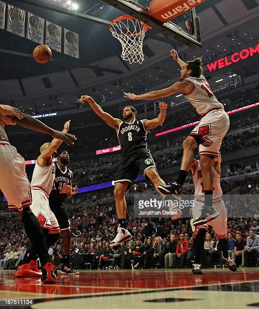 Deron Williams of the Brooklyn Nets passes between Carlos Boozer and Joakim Noah of the Chicago Bulls in Game Three of the Eastern Conference...