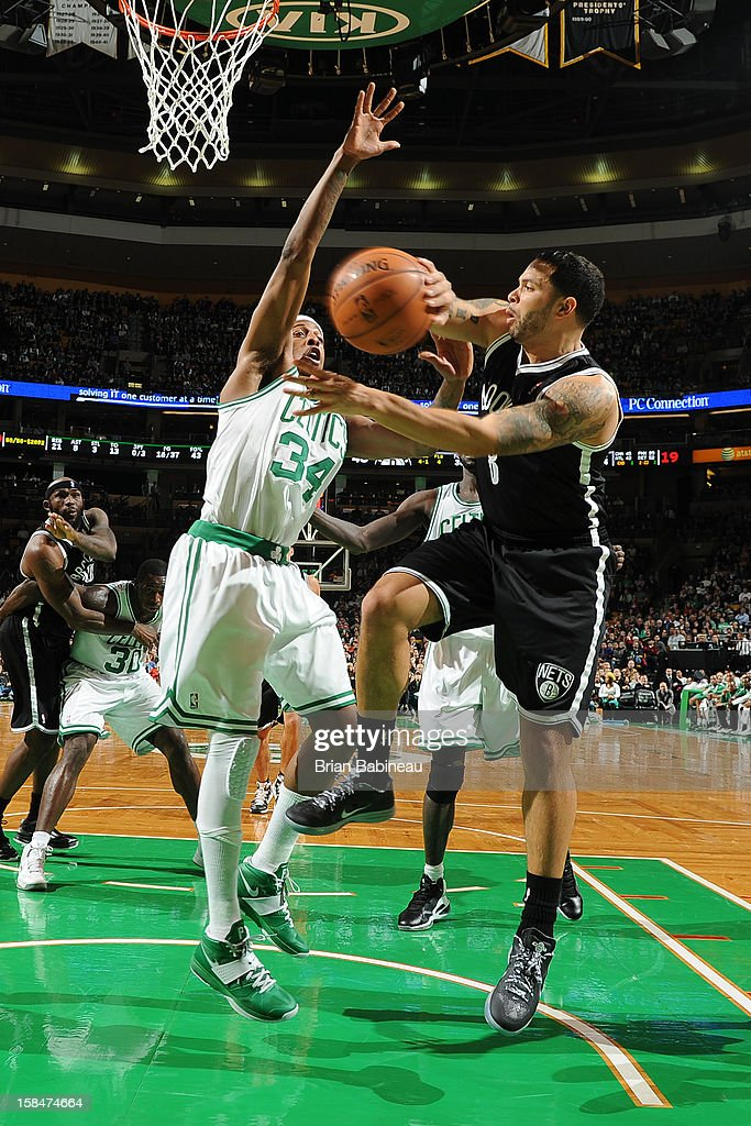 Deron Williams #8 of the Brooklyn Nets passes the ball against Paul Pierce #34 of the Boston Celtics on November 28, 2012 at the TD Garden in Boston, Massachusetts.