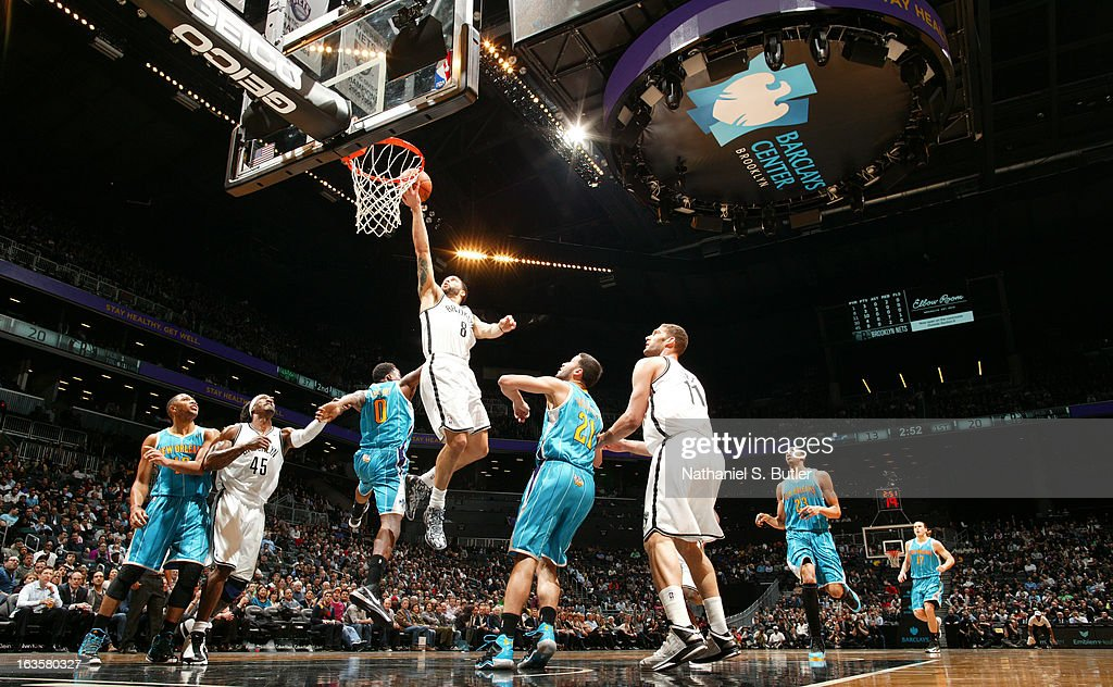 Deron Williams #8 of the Brooklyn Nets shoots a layup against Al-Farouq Aminu #0 and Greivis Vasquez #21 of the New Orleans Hornets on March 12, 2013 at the Barclays Center in the Brooklyn borough of New York City.