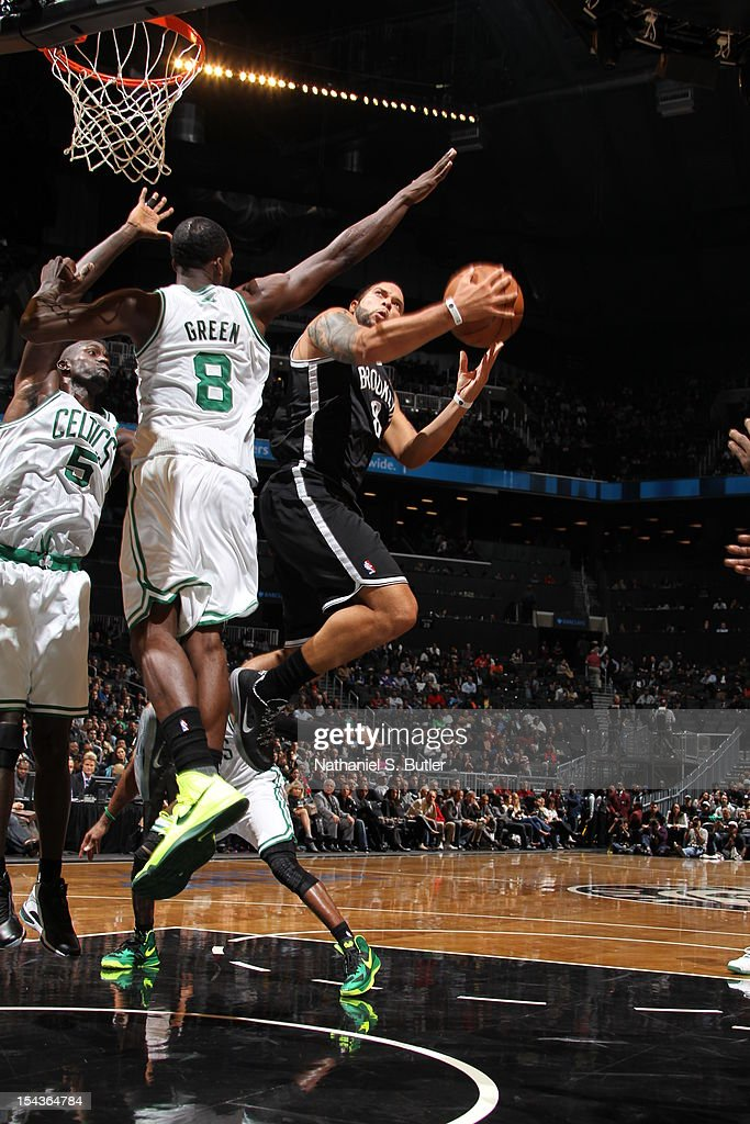 Deron Williams #8 of the Brooklyn Nets shoots against Jeff Green #8 and Kevin Garnett #5 of the Boston Celtics during a pre-season game on October 18, 2012 at the Barclays Center in the Brooklyn borough of New York City.