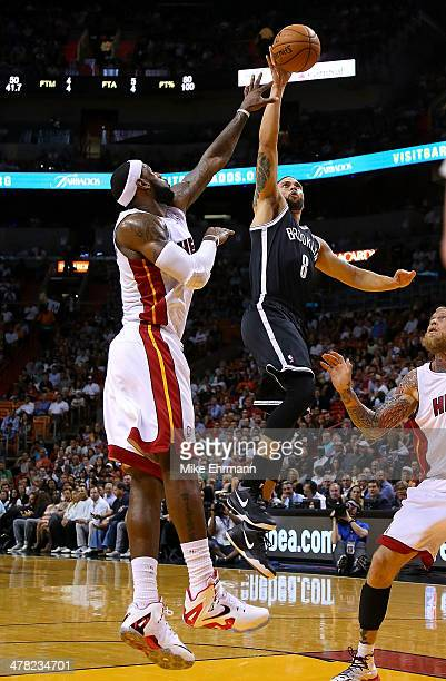 Deron Williams of the Brooklyn Nets shoots over LeBron James of the Miami Heat during a game at American Airlines Arena on March 12 2014 in Miami...