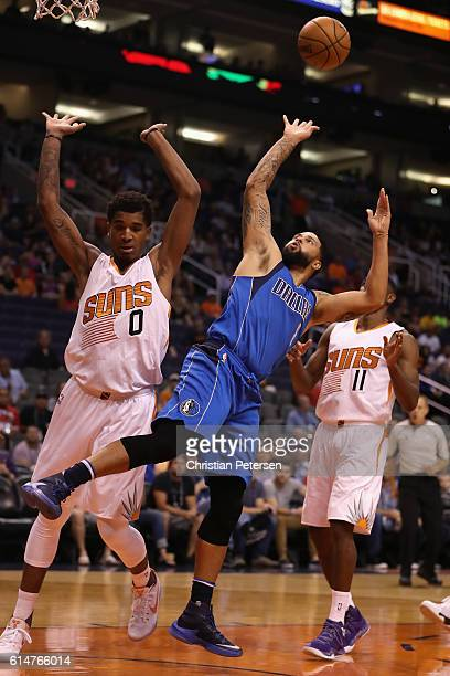 Deron Williams of the Dallas Mavericks attempts a shot past Marquese Chriss and Brandon Knight of the Phoenix Suns during the first half of the...