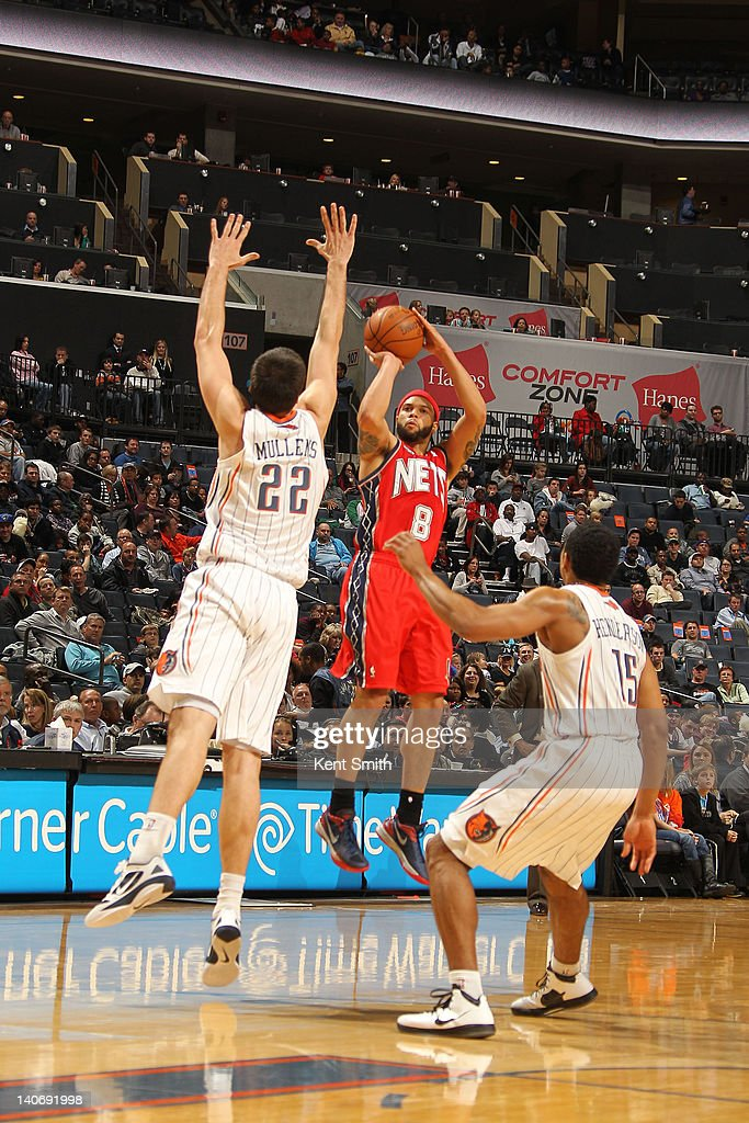 Deron Williams #8 of the New Jersey Nets hits the 3-pointer and then hits the foul shot for a 4 point play against Byron Mullens #22 and Gerald Henderson #15 of the Charlotte Bobcats during the game at the Time Warner Cable Arena on March 4, 2012 in Charlotte, North Carolina.