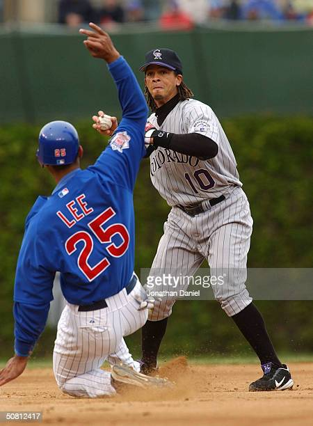 Derrek Lee of the Chicago Cubs slides hard into second base to break up a double play as shortstop Royce Clayton of the Colorado Rockies prepares to...