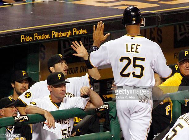 Derrek Lee of the Pittsburgh Pirates celebrates after scoring on a sacrifice fly by Ryan Ludwick against the Cincinnati Reds during the game on...