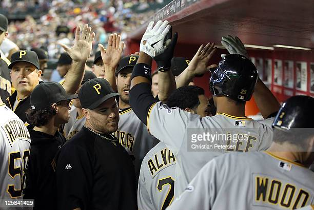 Derrek Lee of the Pittsburgh Pirates highfives teammates after hitting a solo home run against the Arizona Diamondbacks during the sixth inning of...