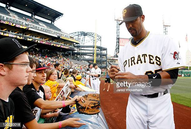 Derrek Lee of the Pittsburgh Pirates newly acquired by trade from the Baltimore Orioles signs autographs for fans before the game against the Chicago...