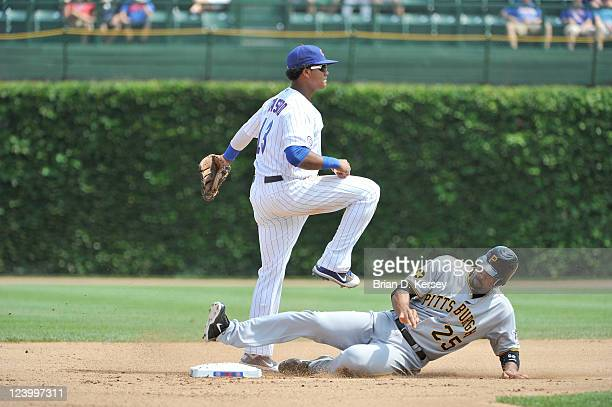 Derrek Lee of the Pittsburgh Pirates slides into second base as shortstop Starlin Castro of the Chicago Cubs throws to first after forcing Lee out at...