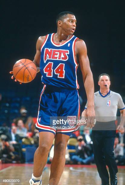 Derrick Coleman of the New Jersey Nets dribbles the ball against the Philadelphia 76ers during an NBA basketball game circa 1992 at The Spectrum in...