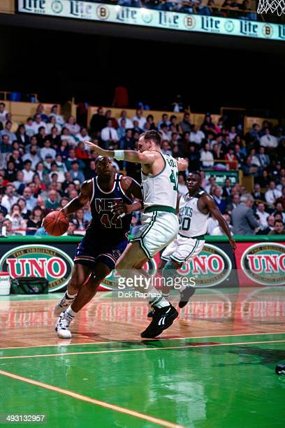 Derrick Coleman of the New Jersey Nets drives against Dino Radja of the Boston Celtics during a game played circa 1994 at the Boston Garden in Boston...
