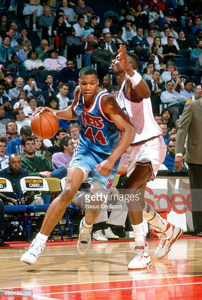 Derrick Coleman of the New Jersey Nets drives on Harvey Grant of the Washington Bullets during an NBA basketball game circa 1991 at the Capital...