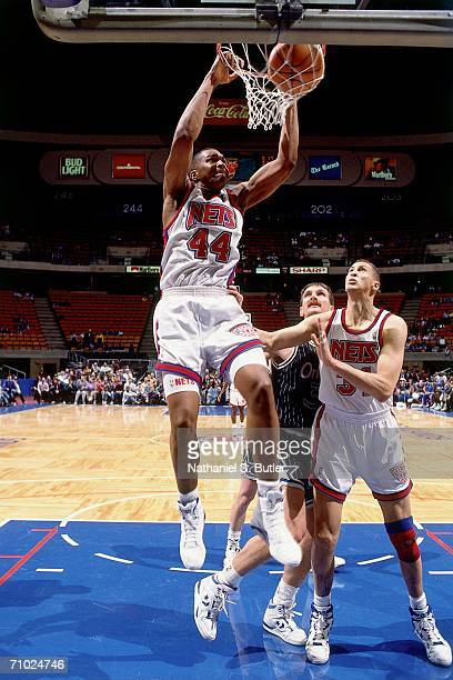 Derrick Coleman of the New Jersey Nets dunks against Jeff Turner of the Orlando Magic during a game played in 1992 at the Brendan Byrne Arena in East...