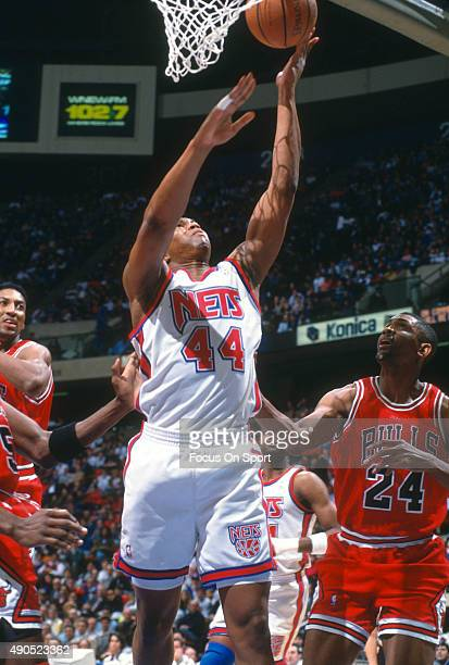 Derrick Coleman of the New Jersey Nets lays the ball up against the Chicago Bulls during an NBA basketball game circa 1992 at the Brendan Byrne Arena...