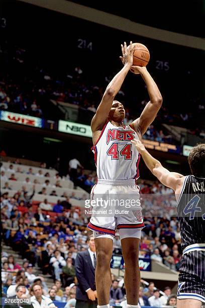 Derrick Coleman of the New Jersey Nets shoots a jump shot against Marck Acres of the Orlando Magic during a game circa 1991 at the Brendan Byrne...