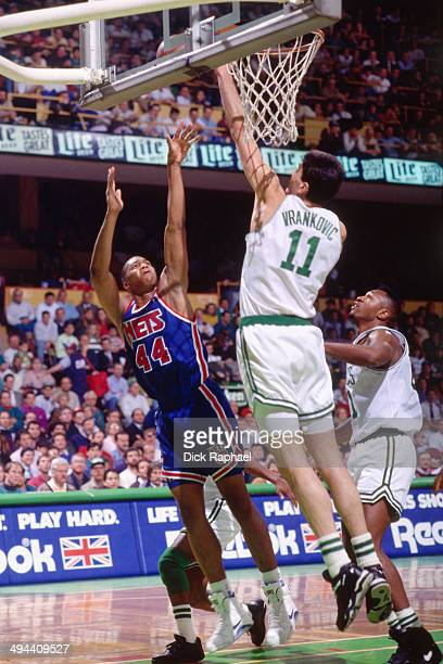 Derrick Coleman of the New Jersey Nets shoots against Stojko Vrankovic of the Boston Celtics during a game played in 1992 at the Boston Garden in...