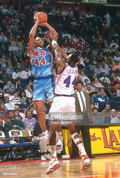Derrick Coleman of the New Jersey Nets shoots over Harvey Grant of the Washington Bullets during an NBA basketball game circa 1991 at the Capital...