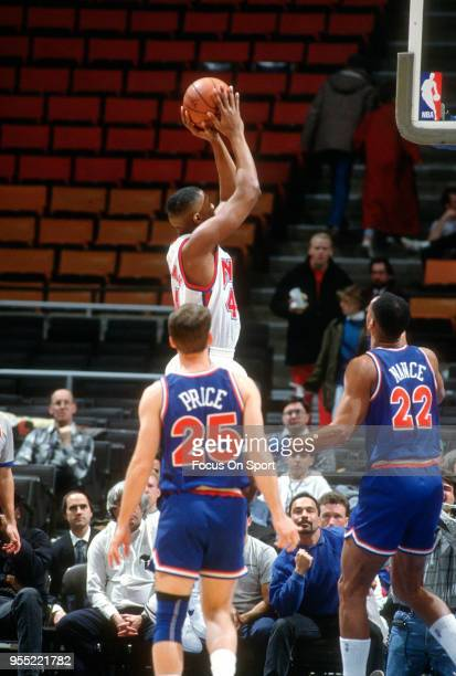 Derrick Coleman of the New Jersey Nets shoots over Larry Nance of the Cleveland Cavaliers during an NBA basketball game circa 1991 at the Brendan...