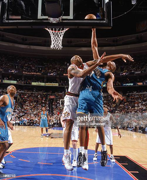 Derrick Coleman of the Philadelphia 76ers puts the pressure on Jamaal Magloire of the New Orleans Hornets during Game One of the Eastern Conference...