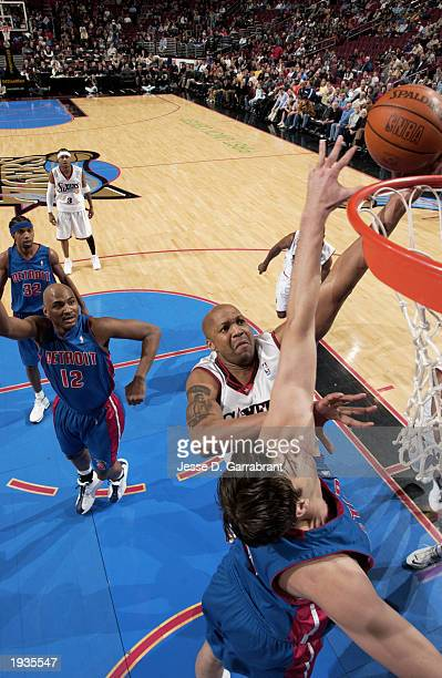 Derrick Coleman of the Philadelphia 76ers shoots a layup over Mehmet Okur of the Detroit Pistons during the game at First Union Center on April 8...